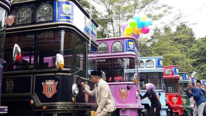 Bapak Ridwan Kamil dan ibu Atalia menandatangani bus bandros